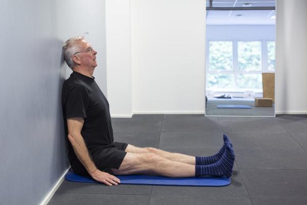 Mann sitter på gulv inntil vegg